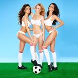 三位美丽的性感的女子足球运动员 免版税库存图片