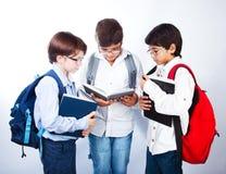 三位逗人喜爱的男小学生读了书 库存图片