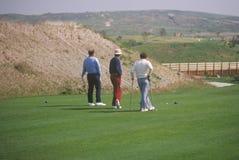 三位高尔夫球运动员走在绿色的,拉古纳Niguel,加州 图库摄影