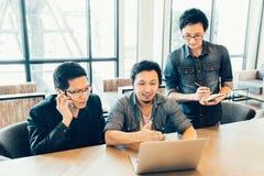 三位年轻亚裔工友或大学生严肃的业务会议或队讨论激发灵感的 免版税库存图片