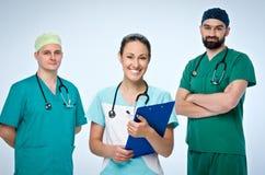 三位年轻医生队  队包括一位医生和一名妇女,两位人医生 他们穿戴洗刷 免版税图库摄影