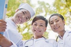 三位医生Smiling和看下来照相机 库存照片
