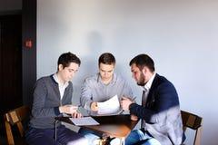 三位年轻男性程序员沟通使用片剂,当sitt时 免版税库存图片