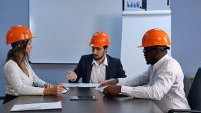 三位建筑师谈论新的项目在办公室 库存图片