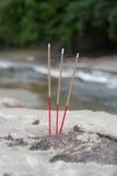 三佛教灼烧的香火在石头黏附在河 库存图片