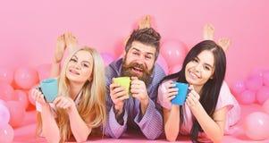 三倍在上午放松用咖啡 床概念的恋人 恋人在床上的喝咖啡 男人和妇女,朋友 免版税库存图片