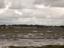 三停泊了在出海口浪潮manningtree的白色小船 免版税库存图片