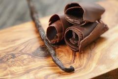 三剥了在橄榄色的木委员会的巧克力卷毛 库存照片