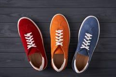 三双绒面革运动鞋顶视图在灰色木板条的 免版税库存照片