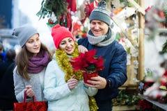 三口之家与选择花卉装饰的十几岁的女孩 免版税库存图片