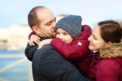 三口之家画象获得乐趣一起由海洋岸和享受看法的 户外 免版税库存照片