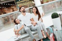 三口之家,父亲、母亲和女儿坐长凳在购物中心 库存照片