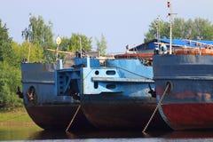三只生锈的货船和被降下的船锚弓在河 免版税图库摄影