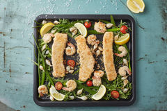 三只fishfingers和虾与菜在烘烤盘子 免版税库存照片