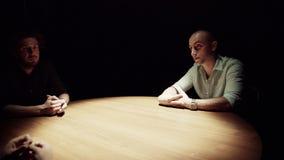 三可爱的年轻人在暗室坐在木桌附近 影视素材