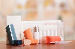 三台吸入器湿剂箱子和医学在抽象桃红色 免版税库存照片