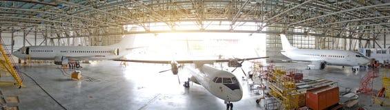 三台客机在有一个开放门的一个飞机棚服务的,全景的看法 免版税库存照片
