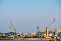 三台重的起重机,两黄色和为装载货船使用的一绿色在口岸 免版税库存图片