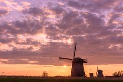 三台风车在日落的晚上,荷兰 库存图片