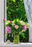 三叶草、矢车菊和茉莉花在一个玻璃花瓶和一块心形的石头花花束在开放风的窗台 免版税库存图片