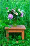 三叶草、矢车菊和茉莉花花花束在一个玻璃花瓶在一个老板凳在绿草中在春天 免版税库存图片
