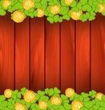 三叶草和金黄硬币在棕色木背景 库存照片
