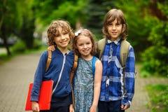 三名一点学校学生、两个男孩和女孩,在容忍的立场在校园 库存图片