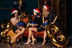 三名俏丽的妇女打开礼物在圣诞晚会 库存图片