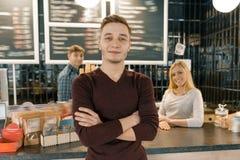 三名咖啡馆工作者年轻队,摆在和微笑对咖啡馆的人们靠近酒吧柜台 配合,职员,小企业, 免版税库存照片