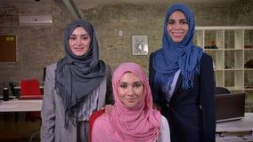 三名在照相机附近的微笑的阿拉伯妇女ar身分和看cwith信心,佩带的另外hijab,在砖 股票视频
