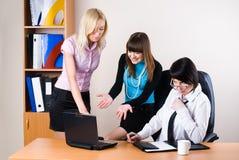 三名女实业家在办公室与膝上型计算机一起使用 库存图片