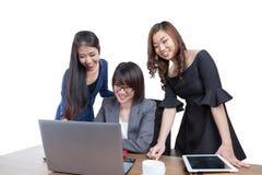 三名女实业家在办公室与膝上型计算机一起使用 图库摄影