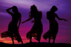 三名妇女剪影比基尼泳装和布裙跳舞的 库存照片