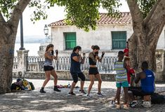 三名妇女和两个孩子在哈瓦那学会如何把外部下来装箱由水在一棵树下 免版税图库摄影