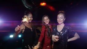 三名妇女跳舞,获得乐趣并且拿着在新年或圣诞晚会的闪烁发光物 股票视频