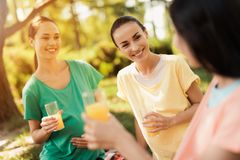 三名孕妇在公园坐在实践瑜伽以后并且喝汁液 他们休息 免版税库存图片