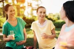 三名孕妇在公园坐在实践瑜伽以后并且喝汁液 他们休息 免版税库存照片