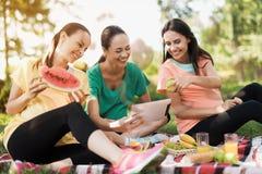 三名孕妇基于自然在做瑜伽以后 他们中的一个举行片剂 图库摄影