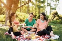 三名孕妇基于自然在做瑜伽以后 他们中的一个举行片剂 免版税图库摄影