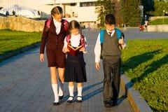 三名学生去公园并且读一本有趣的书 免版税库存图片