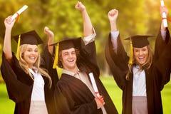 三名学生的综合图象举他们的胳膊的毕业生长袍的 库存图片