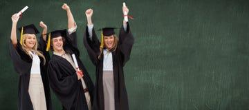 三名学生的综合图象举他们的胳膊的毕业生长袍的 免版税库存照片