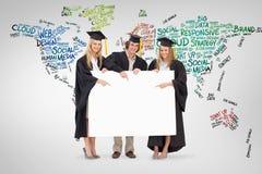 三名学生的综合图象拿着和指向一个空白的标志的毕业生长袍的 免版税库存照片