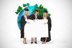 三名学生的综合图象拿着和指向一个空白的标志的毕业生长袍的 库存图片