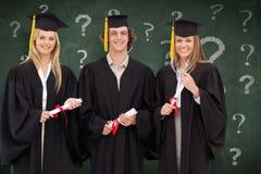 三名学生的综合图象拿着文凭的毕业生长袍的 库存图片