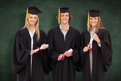 三名学生的综合图象拿着文凭的毕业生长袍的 图库摄影