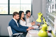 三名工作者看膝上型计算机,当坐在工作场所时 在办公室里面 库存照片