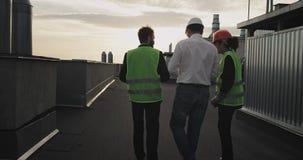 三名工作者转动外籍人并且走向工地工作,美女指向了站点 股票录像