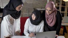 三名年轻回教妇女的队谈论在膝上型计算机的hijab的事务计划,关于项目的交谈在现代 股票视频