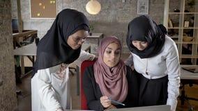 三名年轻回教妇女的队hijab的谈话在膝上型计算机,关于企业项目的交谈在现代办公室 影视素材